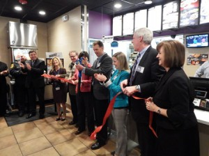 Surrounded by local and state officials, David Lockwood cuts the ribbon at the grand opening of his new Taco Bell. (Photo/Bonnie Adams)