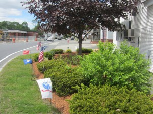 Flags and flowers help beautify the side of the VFW's building.  Photo/Bonnie Adams