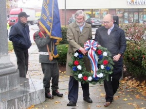Town Moderator John Arnold (left) and Selectman Tim Dodd lay a wreath at the base of the World War 1 monument.