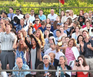 Families and friends cheer for the graduates from the stands.