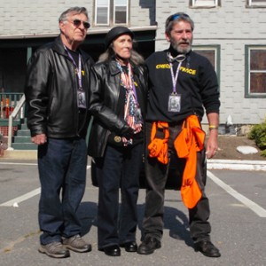 (l to r) Paul Cote, president of the Bikers Helping Bikers Massachusetts Motorcyclists Survivors Fund, stands with Shelly Barnes Hendrix's parents, Roger and Virginia Barnes, as he addresses riders participating in the ride for Shelly.