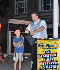Dean Brusnihan, 7, uses a hand bell as a wand to assist Fran Flynn with a magic trick.