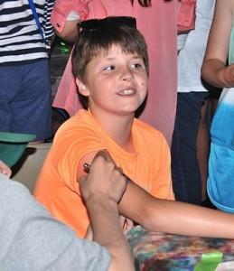 Kyle Martius, 9, gets an airbrush tattoo.