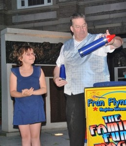 Autumn Campbell, 10, volunteers to assist Fran Flynn with a magic trick.