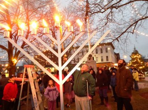 Selectman Denny Drewry lights the final candle on the menorah.