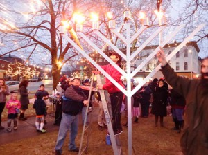 Assisted by Fire Chief Nick Perron (l), Ben Frogel lights the menorah.