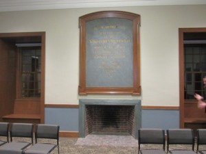 A plaque and fire place in the Board of Selectmen's meeting room