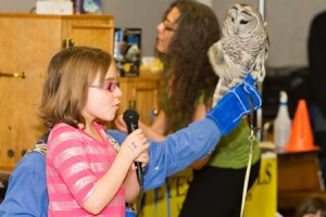 Autumn Campbell, 9, of Westborough, gives a hooting lesson as a Barred Owl watches. (Photo/Jeff Slovin)