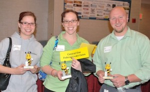 Central One Federal Credit Union teammates (l to r) Bekki Niemiec, Michelle Sheridan and Bryan Stockhaus each receive a trophy as trivia champs