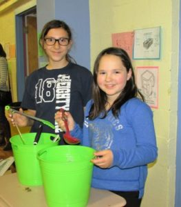Zeh School fourth-graders Juliana Oyola and Siena Sciacca composting fruits and vegetables from lunches.