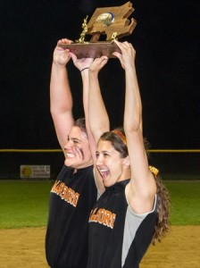 Marlborough High School co-captains Molly McGuire (left) and Marissa Flynn (right) hoist their Central Massachusetts Division 1 Softball trophy aloft for their teammates to see.