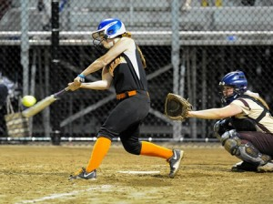 Marlborough High School's Victoria Falco (left) launches her second home run of the night that scored three runs in the fifth inning as Shepherd Hill Regional High School's catcher Marissa Colby is at right.
