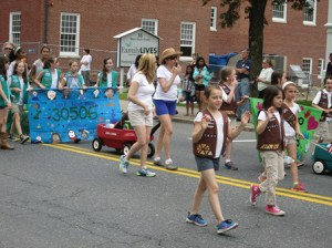 Westborough Girl Scouts wave to the crowd during the Memorial Day parade.